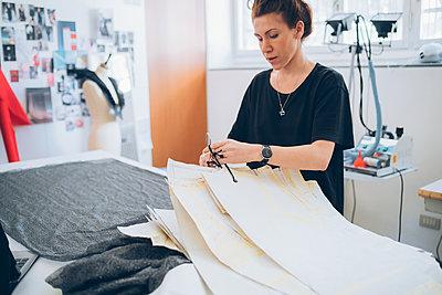 Fashion designer laying out dressmaker's pattern - p429m2058530 by Eugenio Marongiu