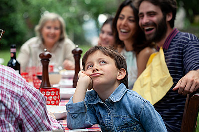 Bored boy at outdoor family meal - p429m2200738 by Sofie Delauw