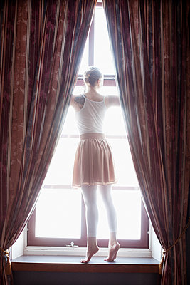 Young woman stands on windowsill - p956m1515490 by Anna Quinn