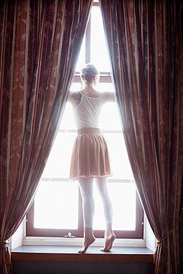 Junge Frau steht auf der Fensterbank - p956m1515490 von Anna Quinn