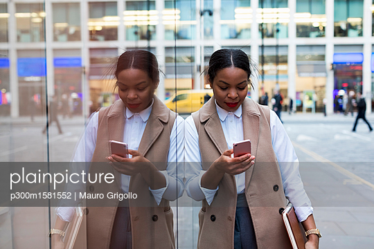 Smiling businesswoman leaning against glass pane looking at cell phone - p300m1581552 von Mauro Grigollo