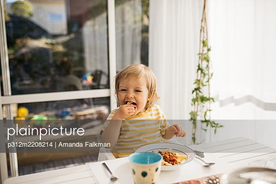 Toddler girl eating at table - p312m2208214 by Amanda Falkman