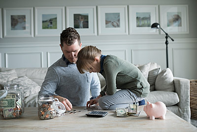 Father teaching daughter counting allowance money in living room - p1192m1231401 by Hero Images