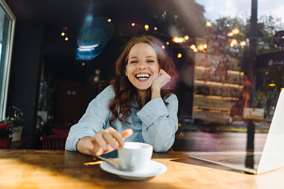 Portrait of happy redheaded woman with laptop in a cafe - p300m2140422 by Kniel Synnatzschke