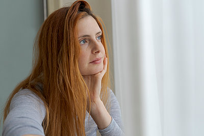 Portrait of serious young woman looking out of window - p300m2179971 by VITTA GALLERY