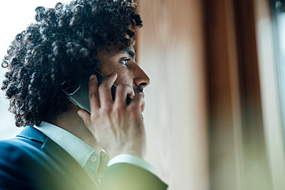 Young businessman with curly black hair talking on mobile phone at office - p300m2243751 by Joseffson