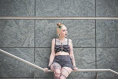 Portrait of young female tattooed punk sitting on subway railing - p429m1013777f by Eugenio Marongiu