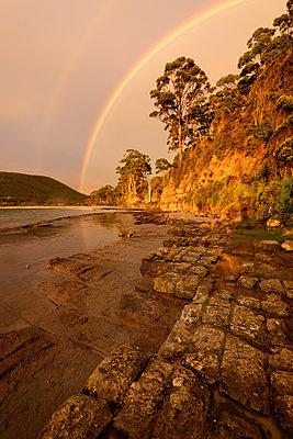 Australia, Tasmania, Eaglehawk Neck, Rainbow over the Tessellated Pavement - p651m2033474 by Christian Heeb