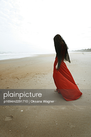Grieving woman in red dress with face covered by black veil walking on the beach barefoot  - p1694m2291710 by Oksana Wagner