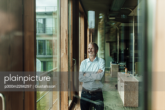 Smiling male business professional with arms crossed looking through window in office - p300m2266297 by Gustafsson