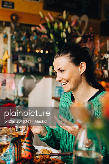 Smiling young woman sitting at table in restaurant during dinner party - p426m2046341 by Maskot