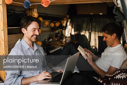 Smiling man using laptop sitting by boyfriend in camping van - p426m2296305 by Maskot