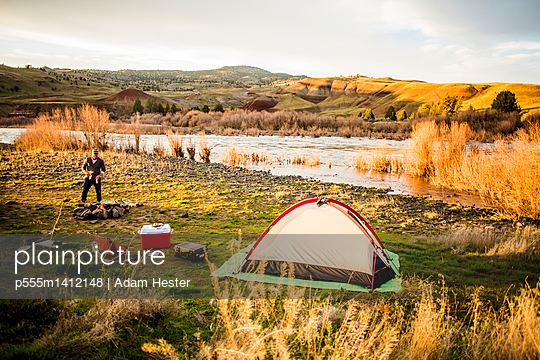 Caucasian man camping near remote river, Painted Hills, Oregon, United States - p555m1412148 by Adam Hester