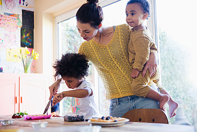 Mother helping toddler daughter cutting breakfast waffles - p1023m2010205 by Sam Edwards