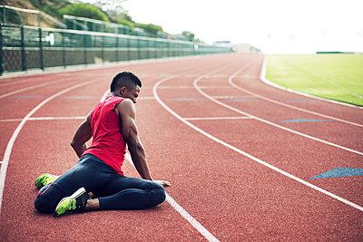 Full length of male athlete exercising on running tracks - p1166m1088129f by John Trice