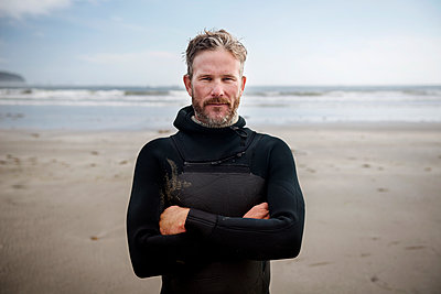 Portrait of mature surfer standing with arms crossed at beach - p1166m1164278 by Cavan Images