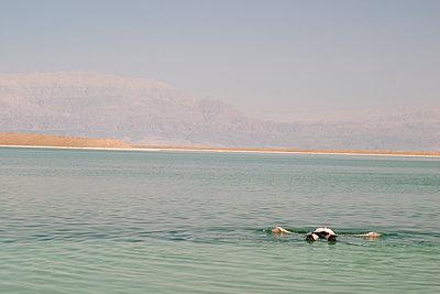 Man floating in Dead Sea, Israel side - p1166m2202241 by Larry Westler