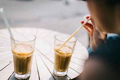 Junge Frau trinkt Eiskaffee in der Sonne im Cafe - p1497m1584591 von Sascha Jacoby