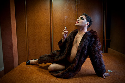 Drag queen sitting on the boss's desk - p1513m2043912 by ESTELLE FENECH