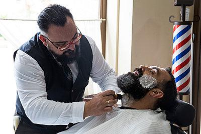 Barber putting shaving foam in man's beard - p300m1205732 by Andrés Benitez