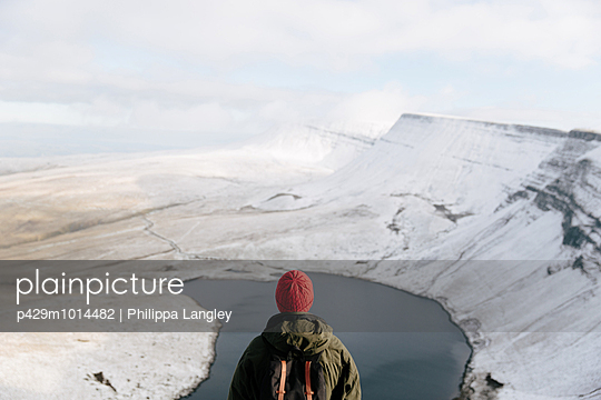 Rear view of man looking at Llyn y Fan Fach, The Brecon Beacons, Wales, UK - p429m1014482 by Philippa Langley