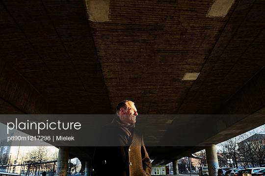 Mann im Mantel steht unter einer Brücke - p890m1217298 von Mielek
