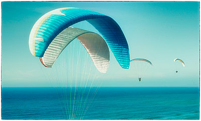 Paragliders over the sea - p1154m1110197 by Tom Hogan