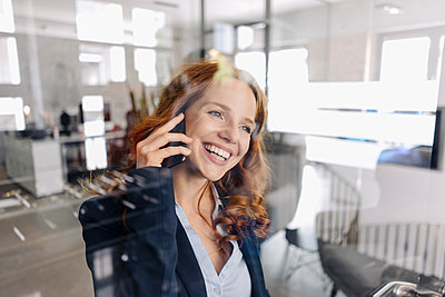 Happy redheaded businesswoman on the phone in office - p300m2140821 by Kniel Synnatzschke