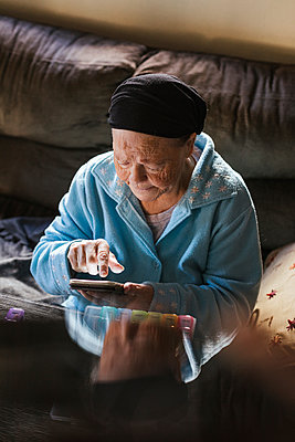 Senior woman using mobile phone in living room - p300m2243110 by DREAMSTOCK1982