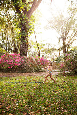 Girl in bathing costume playing in garden sprinkler water - p924m1422699 by Kinzie Riehm