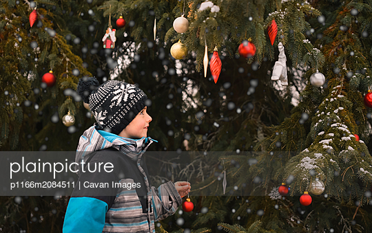 Young boy decorating tree outdoors with Christmas balls in the snow. - p1166m2084511 by Cavan Images