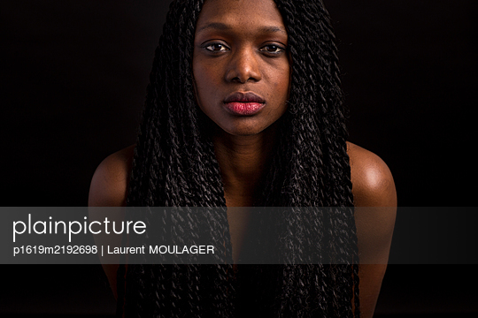 Portrait of a youg woman with braided ahir looking confident at camera - p1619m2192698 by Laurent MOULAGER