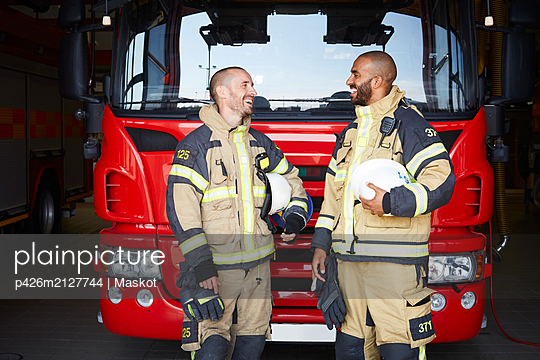 Happy firefighters talking while standing in front of fire engine at fire station - p426m2127744 by Maskot