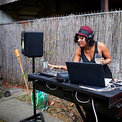Mixed Race dj playing music in backyard - p555m1303245 by Granger Wootz