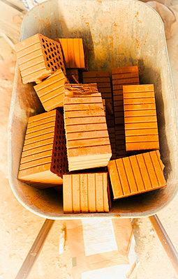Wheelbarrow full bricks construction site orange - p609m1226571 by OSKARQ