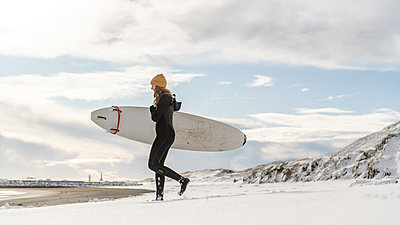 A woman wearing a wetsuit and holding a surfboard walking down a snowy beach and looking out to sea. - p924m2186226 by Alex Eggermont