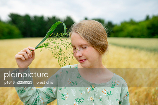 Young woman touching her face with blade of grass, portrait - p1646m2258923 by Slava Chistyakov
