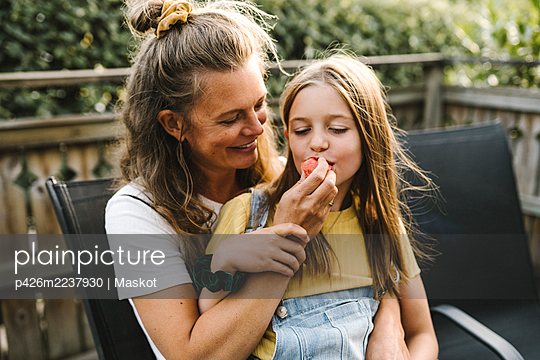 Smiling mother feeding watermelon to daughter while sitting in balcony - p426m2237930 by Maskot