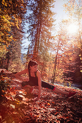 Woman jogging in autumn forest, stretching for warm up - p300m2166372 by Studio 27