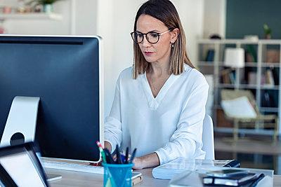Female entrepreneur using laptop in office - p300m2245964 by Josep Suria