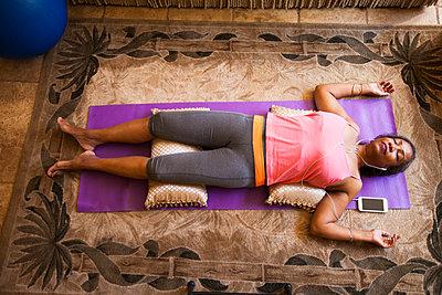 Overhead view of woman lying down meditating - p924m1174875 by Deborah Kolb