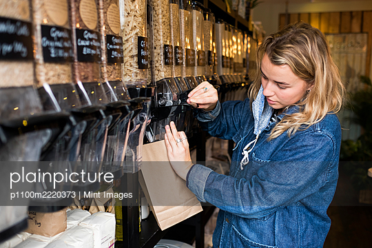 Young blond woman wearing face mask, shopping in waste free wholefood store. - p1100m2220373 by Mint Images