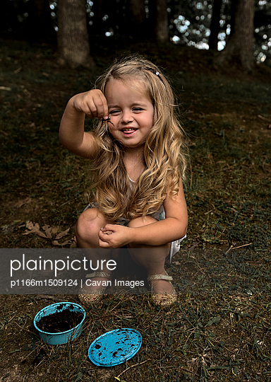 Playful girl holding insect while crouching at forest