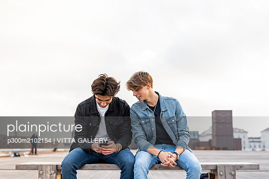 Denmark, Copenhagen, two young men sitting on a bench using cell phone - p300m2102154 by VITTA GALLERY