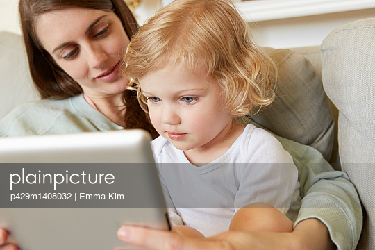 Female toddler sitting on mother's knee looking at digital tablet - p429m1408032 by Emma Kim