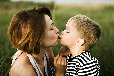 Mother kiss her little son outdoor - p1166m2094799 by Cavan Images