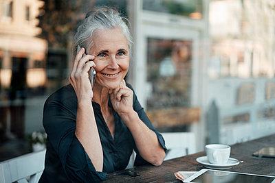 Smiling mature businesswoman talking on mobile phone in cafe - p300m2299286 von Joseffson