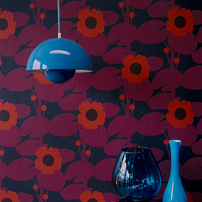 Red patterned wallpaper hanging light and glass home wares - p349m695173 by Emma Lee