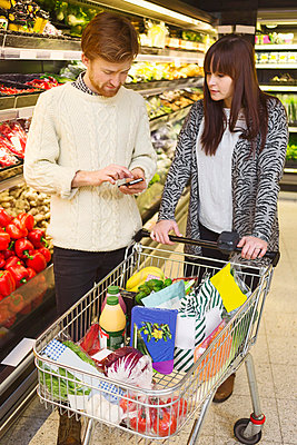 Young couple using mobile phone while buying groceries at supermarket - p426m1017993f by Maskot