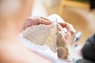 Cropped image of senior woman knitting at nursing home - p426m977471f by Maskot